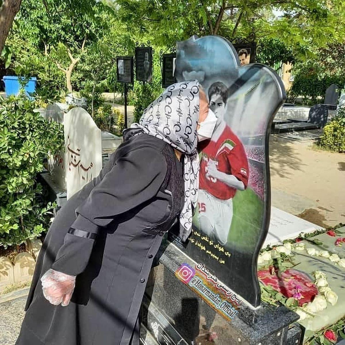 عکسی غم انگیز از بوسه مادر مهرداد میناوند بر سنگ مزار پسرش